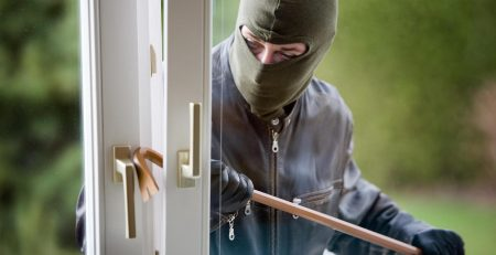 A burglar in a mask using a crowbar to break into a house.