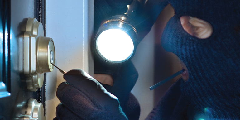 A burglar in a mask using a flashlight and lock pick to compromise a homes security.