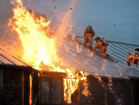 A house fire with fire fighters on the roof.