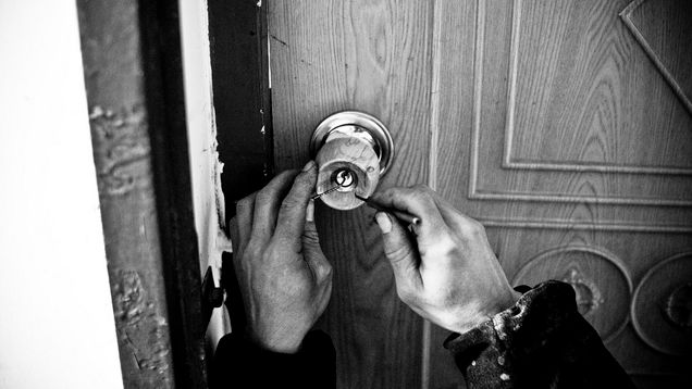 A person using a lock pick to breach someones home security lock.