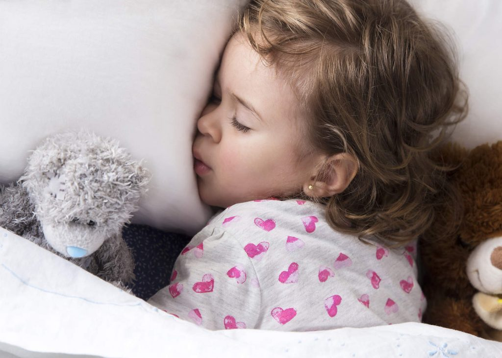Kid sleeping with stuffed animals